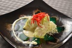 Ρόλοι λάχανων με τη μικτή σαλάτα στο μαύρο πιάτο Στοκ εικόνα με δικαίωμα ελεύθερης χρήσης