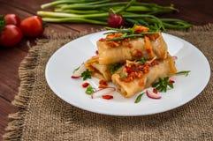 Ρόλοι λάχανων στη σάλτσα ντοματών λευκό πιάτων Ξύλινη ανασκόπηση Στοκ Εικόνες
