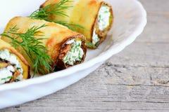 Ρόλοι κολοκυθιών τυριών εξοχικών σπιτιών Το τηγανισμένο κολοκύθι κυλά με το τυρί και τον άνηθο εξοχικών σπιτιών σε ένα πιάτο και  Στοκ Εικόνες
