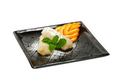Η άνοιξη κυλά με τη μέντα και το πορτοκάλι σε ένα μαύρο πιάτο Στοκ Φωτογραφίες