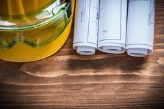 Ρόλοι σχεδιαγραμμάτων γυαλιών ασφάλειας και σκληρό καπέλο στον ξύλινο πίνακα Στοκ Φωτογραφία