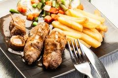 Ρόλοι χοιρινού κρέατος με τις τηγανιτές πατάτες με το λαχανικό Στοκ Εικόνες