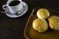 Ρόλοι ψωμιού και ένας μαύρος καφές σε ένα πιάτο Στοκ Εικόνα