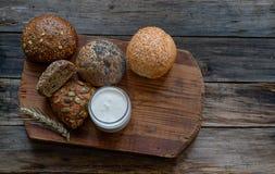 Ρόλοι ψωμιού στην κατάταξη και το γιαούρτι σε έναν ξύλινο πίνακα Στοκ εικόνα με δικαίωμα ελεύθερης χρήσης
