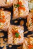Ρόλος σολομών Torched με τη γαρίδα Tempura μέσα Κάλυμμα με το τυρί, τα αυγά γαρίδων Ebiko, Scallion και το άσπρο σουσάμι Στοκ Εικόνες
