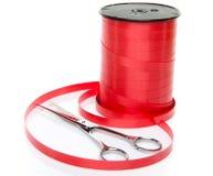 Ρόλος του λαμπρού κόκκινου δώρου κορδελλών με το ψαλίδι Στοκ Φωτογραφία