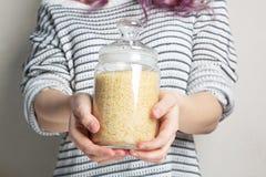 Ρύζι εκμετάλλευσης γυναικών στο βάζο γυαλιού για την αποθήκευση στοκ φωτογραφία με δικαίωμα ελεύθερης χρήσης