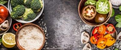 Ρύζι και λαχανικά που μαγειρεύουν τα συστατικά στα κύπελλα στο σκοτεινό αγροτικό υπόβαθρο, έμβλημα Υγιής και χορτοφάγος διατροφή  στοκ φωτογραφίες