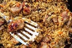 Ρύζι με το βακκίνιο, το βόειο κρέας και τα καρότα σε ένα καζάνι στην πυρκαγιά με ένα ασημένιο κουτάλι Στοκ Φωτογραφίες