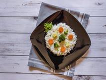 Ρύζι με το λαχανικό στο μαύρο πιάτο στο άσπρο ξύλινο υπόβαθρο Στοκ φωτογραφία με δικαίωμα ελεύθερης χρήσης