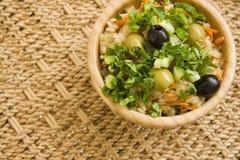 Ρύζι με το παντοπωλείο στο ξύλινο κύπελλο στο υπόβαθρο ινδικού καλάμου στοκ εικόνες