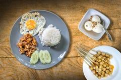 ρύζι με το τηγανισμένο χοιρινό κρέας με το σκόρδο, το τηγανισμένο αυγό και το ταϊλανδικό πράσινο κάρρυ Στοκ Εικόνα