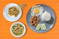 ρύζι με το τηγανισμένο χοιρινό κρέας με το σκόρδο, το τηγανισμένο αυγό και το ταϊλανδικό πράσινο κάρρυ Στοκ εικόνα με δικαίωμα ελεύθερης χρήσης