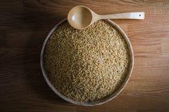 Ρύζι ορυζώνα και ξύλινες κουτάλες στον ξύλινο δίσκο στο ξύλινο υπόβαθρο Στοκ Φωτογραφία