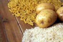 Ρύζι, πατάτες και ζυμαρικά μακαρονιών σε έναν ξύλινο πίνακα Τρεις κοινοί υδατάνθρακες που παρέχουν την ενέργεια αλλά μπορούν να π στοκ εικόνες