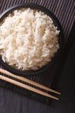 Ρύζι σε μια μαύρη κινηματογράφηση σε πρώτο πλάνο και chopsticks κύπελλων Κάθετη τοπ άποψη Στοκ Εικόνα