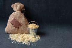 Ρύζι στο σάκο κάδων και burlap στο σκοτεινό υπόβαθρο στοκ εικόνες με δικαίωμα ελεύθερης χρήσης