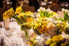 Ρύθμιση λουλουδιών σε έναν κομψό πίνακα γευμάτων Στοκ Φωτογραφία