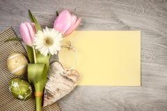 Ρύθμιση Πάσχας με τα λουλούδια και τα αυγά στο ξύλο Στοκ Εικόνες