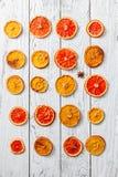 Ρύθμιση των ξηρών πορτοκαλιών στο άσπρο ξύλινο υπόβαθρο Στοκ Εικόνες