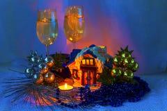 Ρύθμιση Χριστουγέννων με την κεραμικά καμπίνα, τα κεριά, τα γυαλιά κρασιού και τις διακοσμήσεις Χριστουγέννων. Στοκ Φωτογραφία