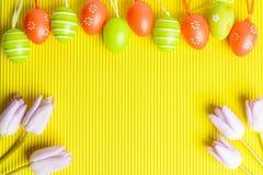 Ρύθμιση χρωματισμένων των Πάσχα αυγών και των τουλιπών στο κίτρινο backgro Στοκ Φωτογραφίες