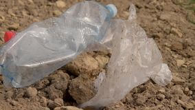 Ρύπανση των πλαστικών στο έδαφος Τα πλαστικά απόβλητα βρίσκονται στο έδαφος Προστασία του περιβάλλοντος Πλαστικά μπουκάλια και άλ απόθεμα βίντεο