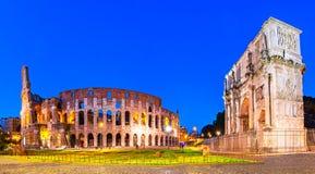 Ρώμη, Ιταλία: Άποψη νύχτας της αψίδας του Constantine δίπλα στο Colosseum μετά από το ηλιοβασίλεμα πέρα από έναν μπλε ουρανό στοκ εικόνες