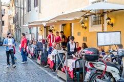 Ρώμη, Ιταλία - τον Οκτώβριο του 2015: Εστιατόριο καφέδων στην αρχαία στενή οδό στη Ρώμη, Ιταλία όπου οι ταξιδιώτες κατανάλωσης κα Στοκ Φωτογραφίες