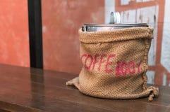 Σάκος καφέ στον ξύλινο πίνακα στοκ φωτογραφία με δικαίωμα ελεύθερης χρήσης