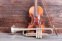 Σάλπιγγα και βιολί στο ξύλινο υπόβαθρο στοκ εικόνες με δικαίωμα ελεύθερης χρήσης