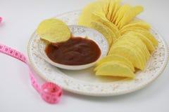 Σάλτσα ντοματών και τσιπ πατατών στο πιάτο Διατροφή, πάχυνση στοκ εικόνα