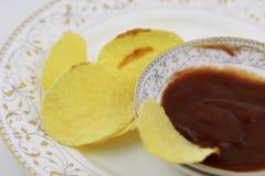 Σάλτσα ντοματών και τσιπ πατατών στο πιάτο Διατροφή, πάχυνση στοκ φωτογραφία