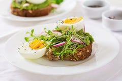 Σάντουιτς αυγών αβοκάντο με ολόκληρο το ψωμί σιταριού στο άσπρο ξύλινο υπόβαθρο στοκ εικόνα