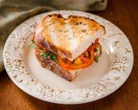 Σάντουιτς βασιλικού ντοματών στο ψημένο ψωμί στοκ εικόνα