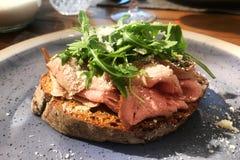 Σάντουιτς βόειου κρέατος ψητού σε ένα πιάτο σε ένα εστιατόριο Εξυπηρετούμενος πίνακας στοκ εικόνες με δικαίωμα ελεύθερης χρήσης