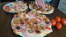 Σάντουιτς (καναπεδάκια) του σαλαμιού σε ένα πιάτο απόθεμα βίντεο