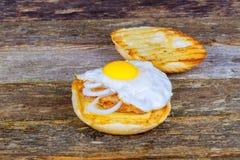 Σάντουιτς με ένα τηγανισμένο αυγό, ένα μπέϊκον, ένα τυρί και τα λαχανικά στοκ εικόνα με δικαίωμα ελεύθερης χρήσης