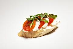 Σάντουιτς με τη μοτσαρέλα, την ντομάτα και το arugula στο γκρίζο υπόβαθρο Στοκ Φωτογραφίες