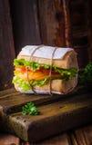 Σάντουιτς με τη σαλάτα φύλλων και ντομάτες στο ξύλινο baskgraund Εκλεκτική εστίαση Στοκ φωτογραφία με δικαίωμα ελεύθερης χρήσης