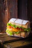 Σάντουιτς με τη σαλάτα φύλλων και ντομάτες στο ξύλινο baskgraund Εκλεκτική εστίαση Στοκ Εικόνα