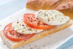 Σάντουιτς με τις τεμαχισμένες φρέσκες ντομάτες και τη μοτσαρέλα Στοκ Φωτογραφία