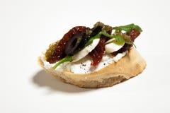 Σάντουιτς με το άσπρο τυρί, την ξηρά ντομάτα, τις ελιές και το arugula επάνω Στοκ Φωτογραφία