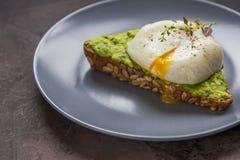 Σάντουιτς με το αβοκάντο και το λαθραίο αυγό πρόγευμα υγιές Στοκ Εικόνες