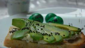 Σάντουιτς με το αβοκάντο που ψεκάζεται με το μαύρο σουσάμι φιλμ μικρού μήκους