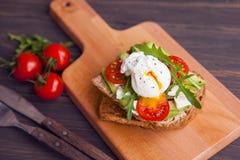 Σάντουιτς με το αυγό στη φρυγανιά με τις ντομάτες τυριών χορταριών Στοκ Φωτογραφίες