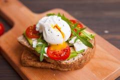 Σάντουιτς με το αυγό στη φρυγανιά με τις ντομάτες τυριών χορταριών Στοκ Εικόνες