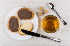 Σάντουιτς με το βούτυρο σοκολάτας, ζάχαρη, κουταλάκι του γλυκού, φλυτζάνι του τσαγιού, Κ Στοκ Φωτογραφίες