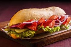 Σάντουιτς με το ζαμπόν, το κρεμμύδι, το μαρούλι και τα τουρσιά σε έναν ξύλινο πίνακα Στοκ εικόνα με δικαίωμα ελεύθερης χρήσης