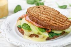 Σάντουιτς με το ζαμπόν, brie το τυρί ή Camembert, το σπανάκι, τη Apple και τη μουστάρδα Στοκ Εικόνα